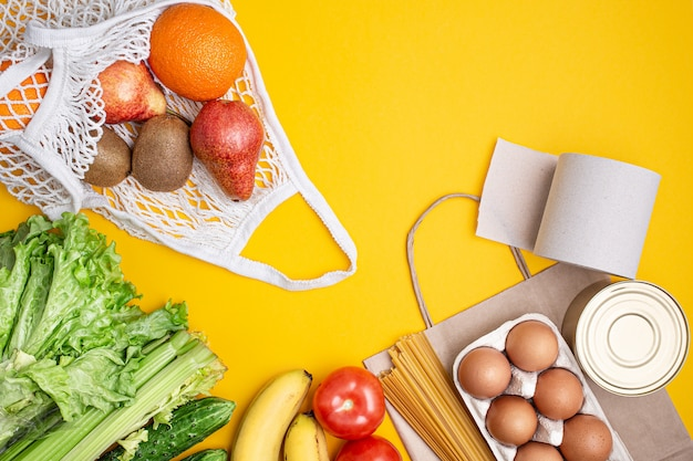 Paper bag with food, canned food, tomatoes, cucumbers, bananas on a yellow background.