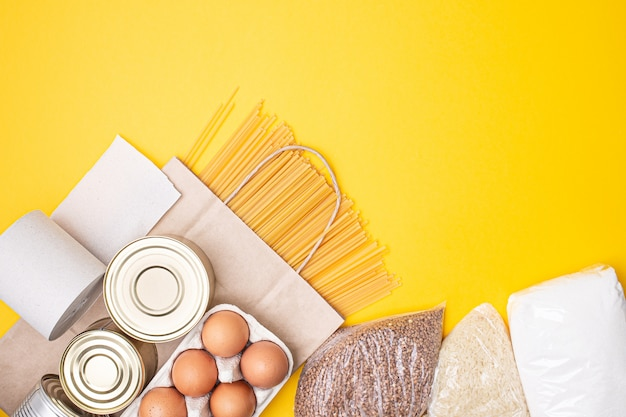 Paper bag with food, canned food, tomatoes, cucumbers, bananas on yellow background.