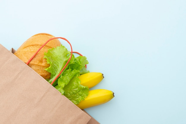 Paper bag with food: green leaves of salad, bread and banana. lay out on blue background, top view