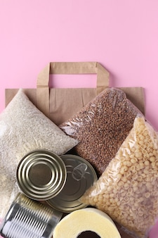 ピンクの表面に隔離期間中の食料品の危機食料ストック付き紙袋。ご飯、そば、パスタ、缶詰、トイレットペーパー。フードデリバリー、寄付、縦書き、トップビュー