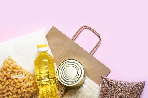 Бумажный пакет с продовольственными товарами для карантина. макаронные изделия, гречка, сахар, рис, крупы, консервы. пожертвование. вид сверху