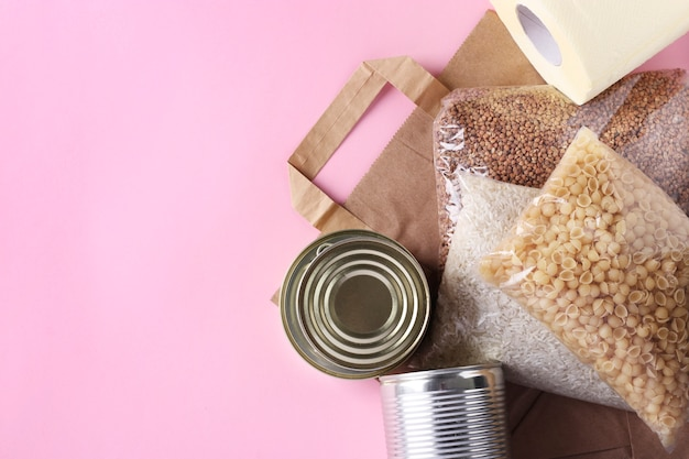 Paper bag with food supplies crisis food stock for quarantine isolation period on pink wall. rice, buckwheat, pasta, canned food, toilet paper. food delivery, donation, copy space, closeup