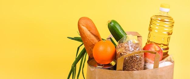 黄色の背景に食料品の紙袋