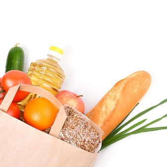 Paper bag with food supplies for the period of quarantine isolation on a white . copyspace.