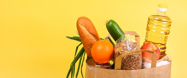 Paper bag with food supplies on yellow background