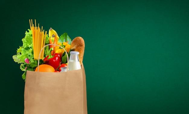 緑の背景に新鮮で健康的な食料品が入った紙袋