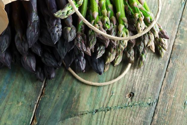 木製の背景に摘みたての生有機天然パープルアスパラガスの槍と紙バッグ。