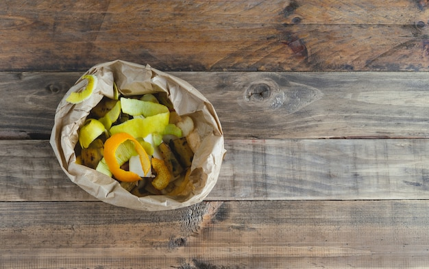 Paper bag with fruit peels for composting on wooden background.