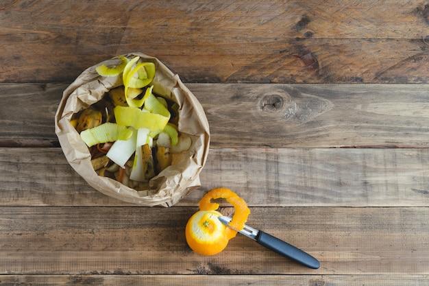 퇴비화를 위해 나무 바닥에 과일 껍질이 있는 종이 봉지.