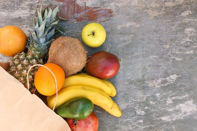 古い木製の背景に果物と野菜の紙袋。上面図。