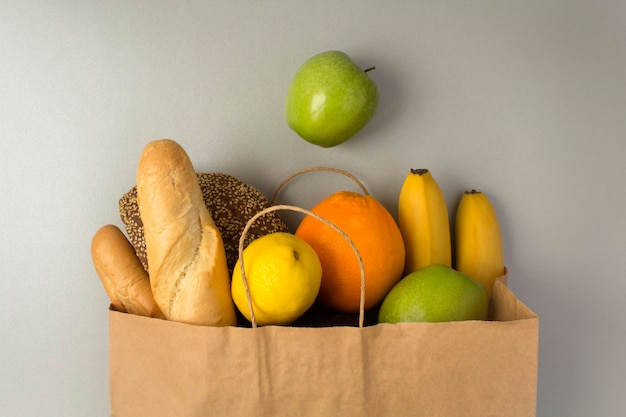 Paper bag  with fruits and bread on the gray surface