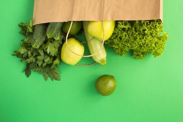緑の表面に緑の野菜と果物が入った紙袋。バッグ食品のコンセプト。トップビュー。コピースペース。