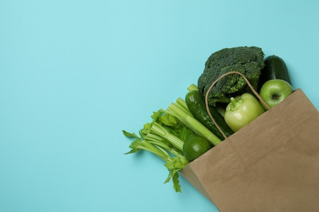 Paper bag with green vegetables on blue