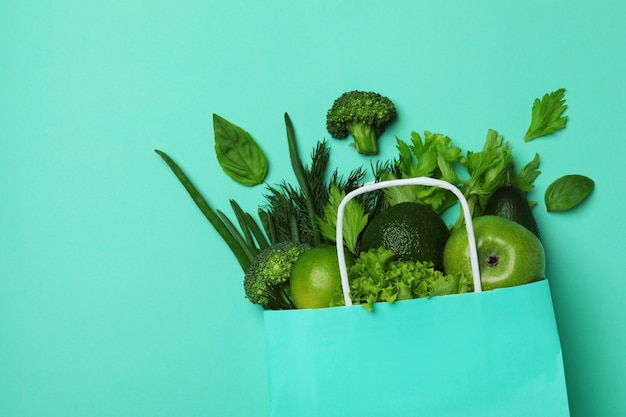 Paper bag with green vegetables on mint