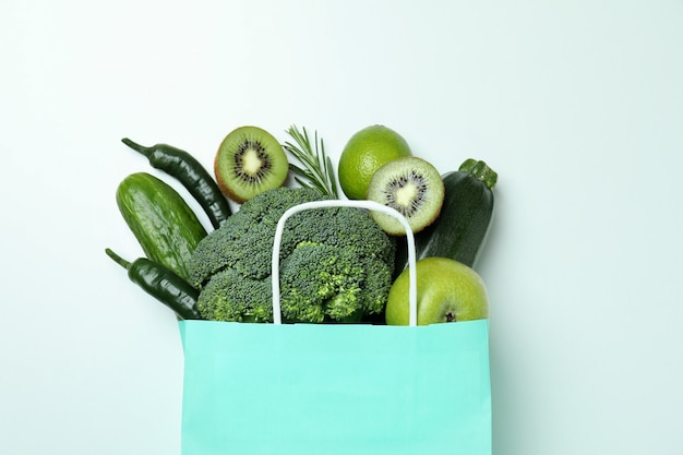 Paper bag with green vegetables on white