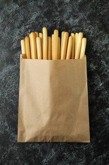 黒の煙のような背景にグリッシーニブレッドスティックと紙袋