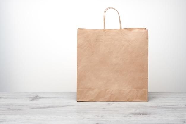 Бумажный пакет с изолированными ручками. бумажный пакет крафт на деревянном столе.
