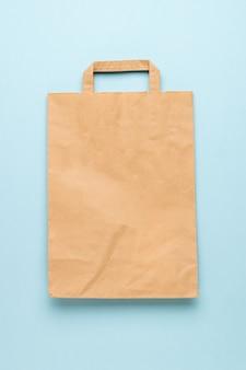 青い表面にハンドルが付いた紙袋。普遍的な環境に優しい包装。フラットレイ。