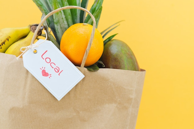 Paper bag with label with word local with assorted fruit on yellow background.