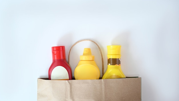 白い背景で隔離のソースボトルと紙袋。