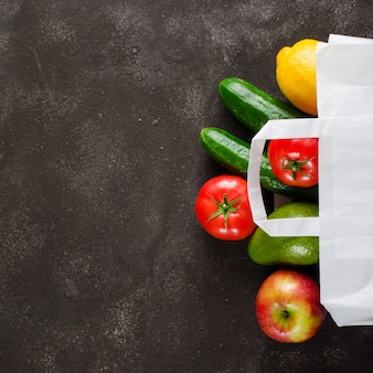 Paper bag with various groceries on dark concrete background. food delivery concept.