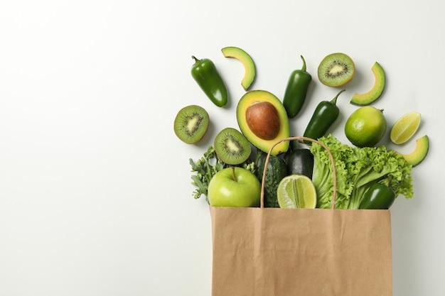 野菜と果物の白い背景の上の紙バッグ