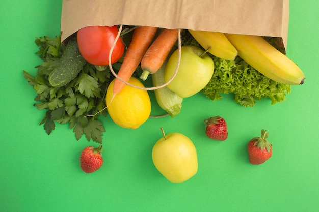 野菜、果物、バゲット、緑の背景、上面図、コピー領域の紙袋