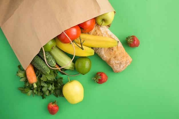 緑の表面に野菜、果物、バゲットが入った紙袋。バッグ食品のコンセプト。トップビュー。コピースペース。