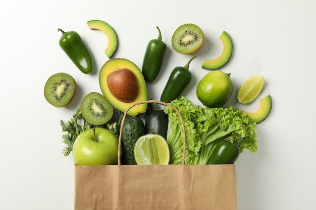 Paper bag with vegetables and fruits on white