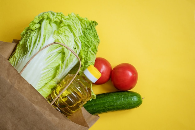Paper bag with vegetables and oil on a yellow background