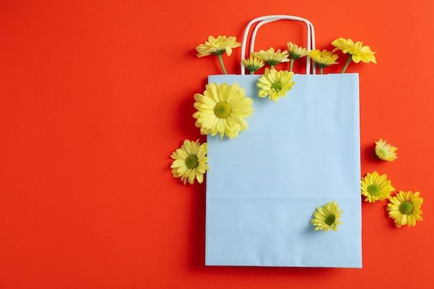 Бумажный пакет с желтыми хризантемами на красном фоне.