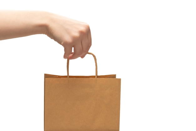 Paper bag in woman hands isolated on white background.