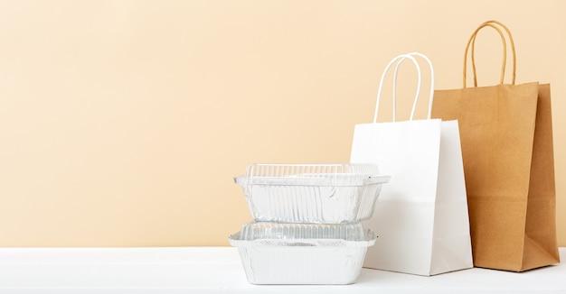 종이 가방 및 흰색 테이블에 식품 용기. 음식 배달 서비스. 호일 용기에 담긴 테이크 아웃 식품, 빈 판지 종이 포장.