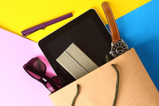 紙袋、眼鏡、時計、ペン、タブは、いくつかの紙の背景に置かれます。