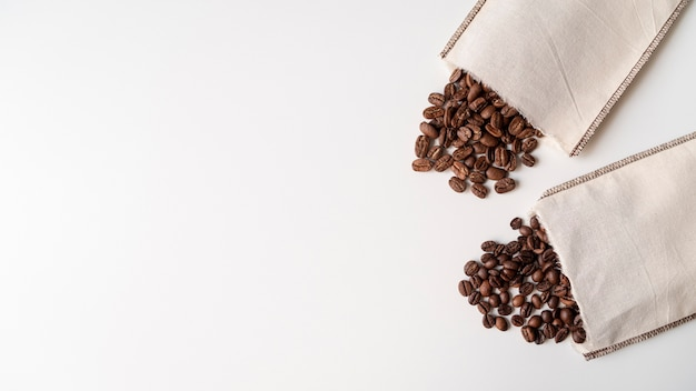 Paper bags with coffee beans white surface