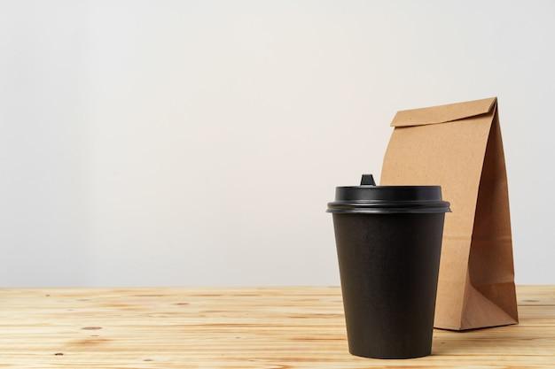 持ち帰り用の食品とコーヒーカップの容器が入った紙袋。弁当箱