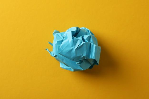 Бумажный шарик на желтом фоне, крупный план