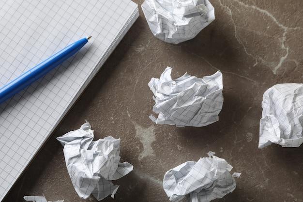 Бумажные шарики, блокнот и ручка на сером столе, крупным планом