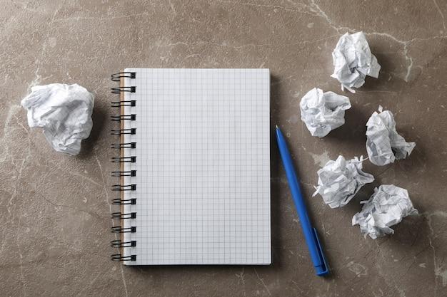 Бумажные шарики, блокнот и ручка на сером столе, вид сверху