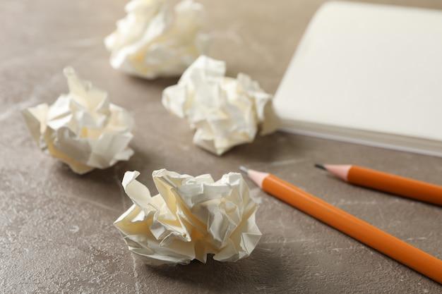 Бумажные шарики, блокнот и карандаши на сером столе, крупным планом