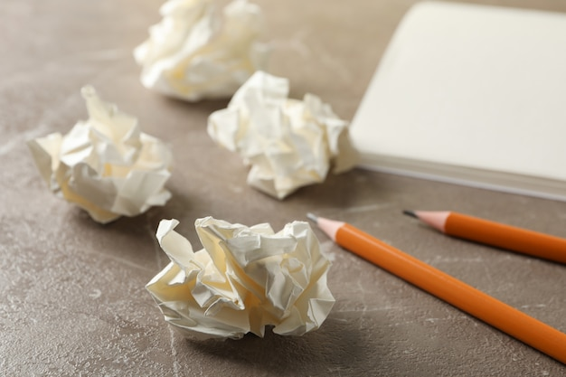 Paper balls, notebook and pencils on grey table, close up
