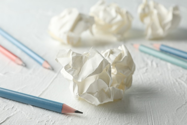 Paper balls and pencils on white table, close up