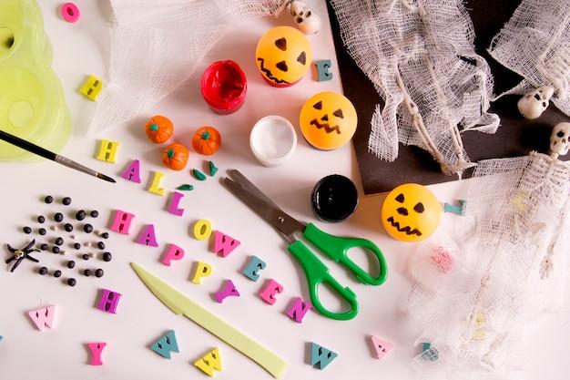 木製のテーブルに絵の具で紙、包帯、粘土。ハロウィーンのグリーティングカードのクモとクモの巣、幽霊のスケルトン。子供のための工芸品