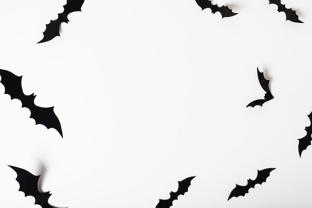 Paper bats hanging on white wall