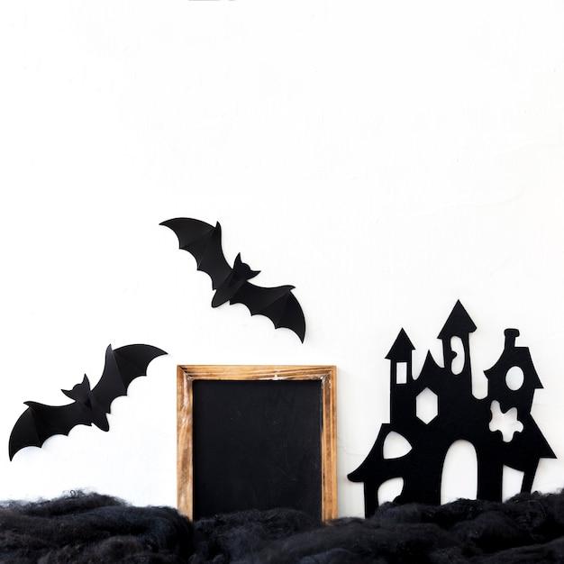 Paper bats near castle and chalkboard