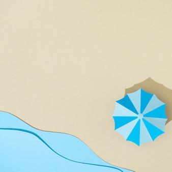 Бумажный пляж с зонтиком и морем.