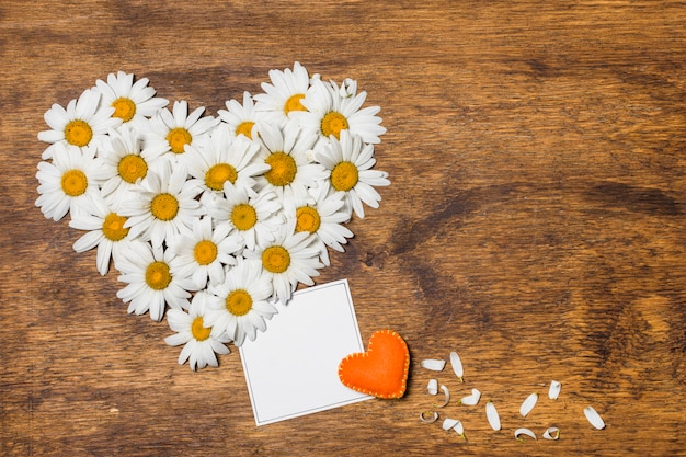 흰 꽃과 오렌지 장난감의 관상 심장 사이의 종이