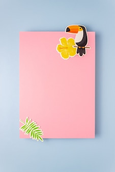 Paper bird and palm tree branch on blank pink card or note. minimal concept.