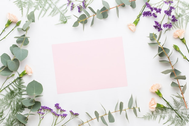 Заготовка бумаги, цветы гвоздики, ветви эвкалипта на пастельном фоне