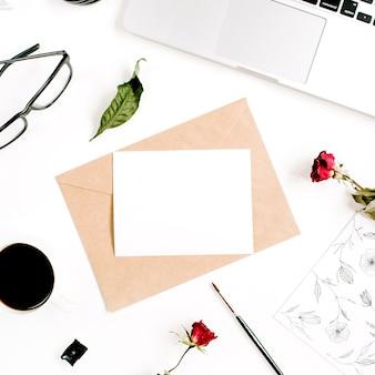 Заготовка бумаги, крафт-конверт, красные розы, ноутбук, кофе на белой поверхности